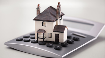 Photograph of a model house on top of a calculator.